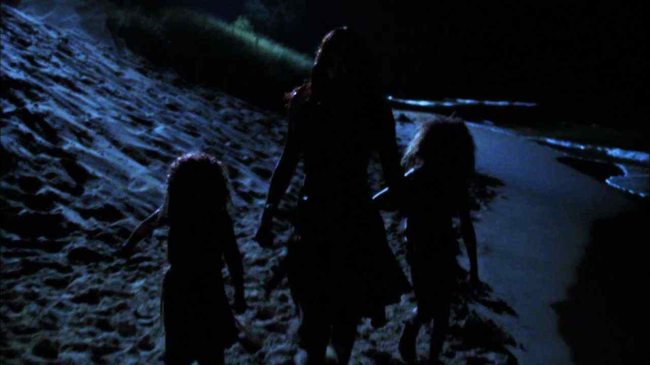 The cannibal family walks on the beach back to their cave in Offspring. The  Woman