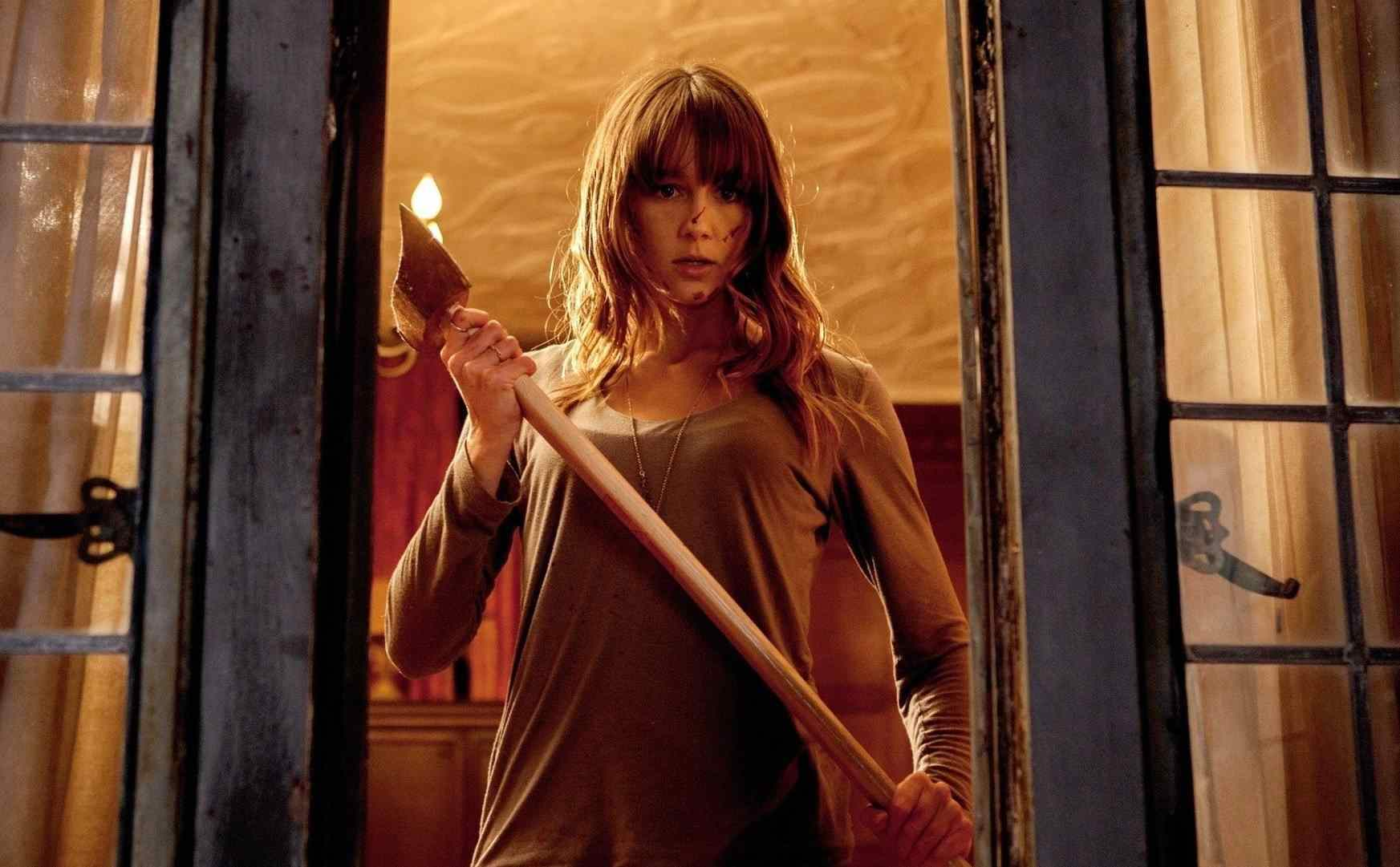 Erin holding an axe at the window in You're Next.