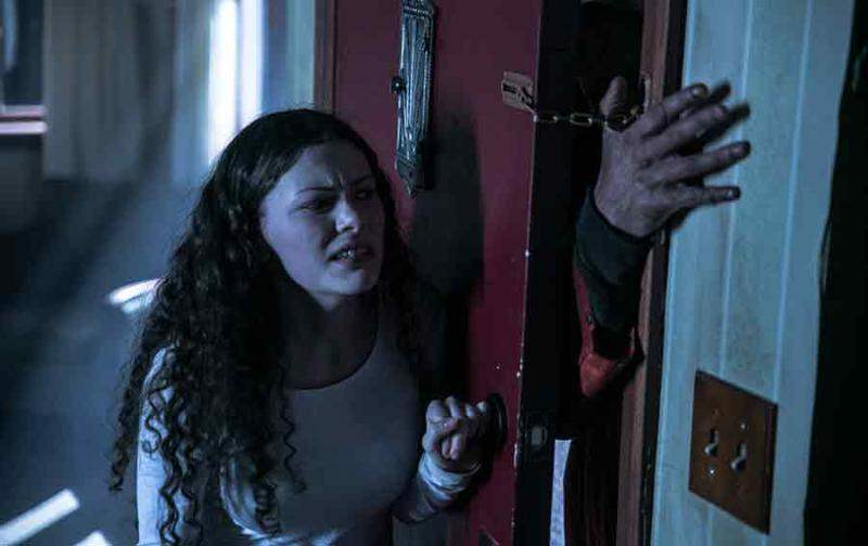 Emily fights off the killer coming through her front door in Suspension.