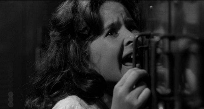 A panicked Nancy runs from Cady in the school in 1962's Cape Fear.