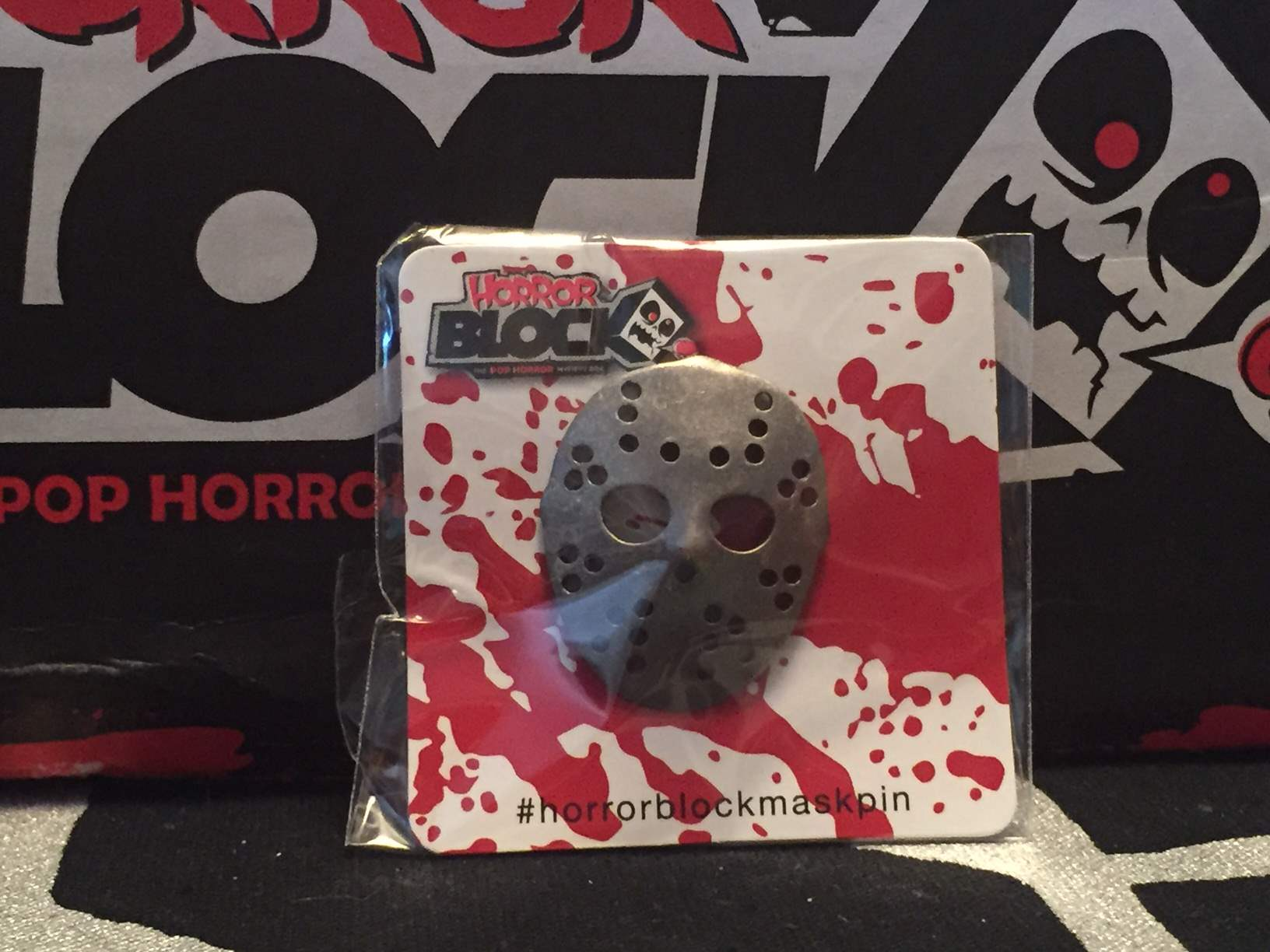 A silver hockey mask pin in the May 2016 Horror Block