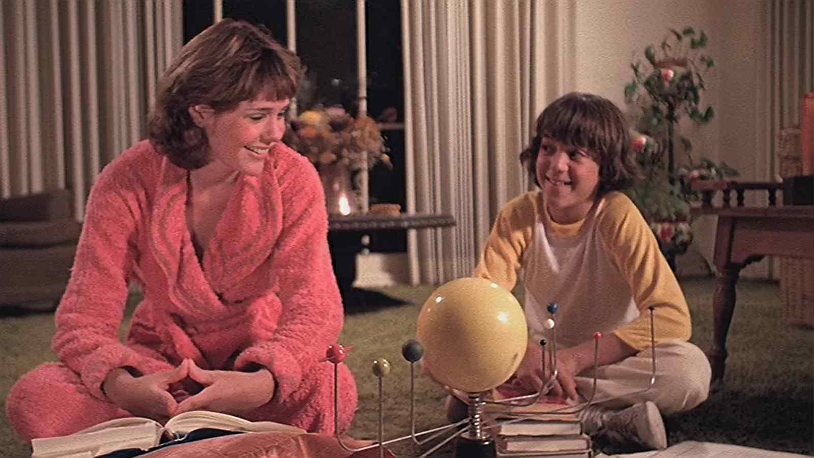 Joyce (Lori Lethin) and her brother Timmy (K.C. Martel) doing some research on astrology in Ed Hunt's Bloody Birthday.