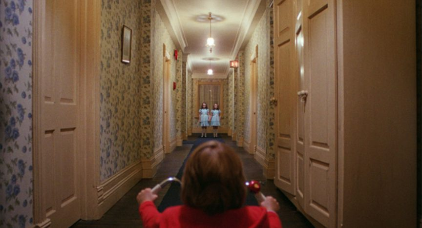 Danny and twin girls in hallway in Kubrick's The Shining